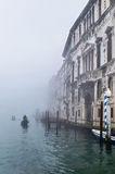 Foggy (misty) Venice. Canal, historical, houses and gondoliers with gondolas on thick fog. Royalty Free Stock Image