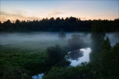 Foggy morning. Early morning. Early in the morning the fog hangs on a green meadow about the river Royalty Free Stock Photos
