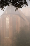 Foggy morning around the church Stock Photos