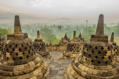 Foggy morning in Borobudur, Java, Indonesia. Borobudur, Java, Indonesia - November 22, 2015: Foggy morning in Borobudur temple with view on stupas. In the Stock Photos