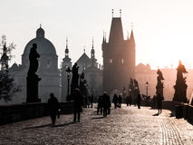 Foggy morning on Charles Bridge, Prague, Czech Republic. Sunrise with silhouettes of walking people, statues and Old stock image