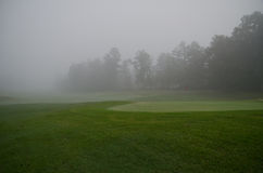 Foggy Morning on the Green. Foggy view of a  golf hole, with a red flagstick Royalty Free Stock Photography