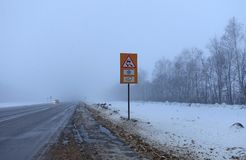 Foggy morning on the highway. Hazard warning sign on the sidelines. Car headlights away on the road royalty free stock image
