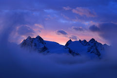 Foggy morning in Italian Alps, early morning in the mountain with snow during violet twilight, hills in the clouds Royalty Free Stock Photos