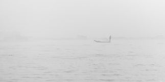 Foggy morning lake and fisherman Stock Images