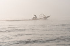 Foggy morning lake and fisherman on motor boat Stock Photo
