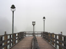 Foggy morning on Lake Konigssee (King's lake) in Bavaria, German. A wooden pier by lakeside. Watch, two lamppost stock image
