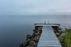 Foggy morning on the lake with pier on foreground. Finland royalty free stock photo