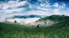 Foggy morning landscape. Foggy morning summer mountain landscape with mist and green meadow. Rural houses in the fog and dramatic cloudy sky. Carpathians Stock Photos