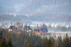 Foggy morning mist over mountain valley with wooden rural farm house buildings. High Tatra, Carpathians, Poland Stock Images