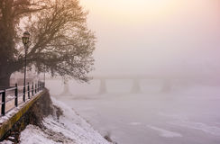Foggy morning near the bridge through the frozen river. Tree in hoarfrost on the snowy empty embankment. gorgeous cityscape sunrise Stock Images