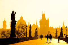 Foggy Morning On Charles Bridge, Prague, Czech Republic. Sunrise With Silhouettes Of Walking People, Statues And Old Stock Photography