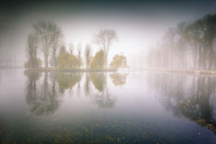 Foggy morning panorama in the autumn park near the lake. Stock Photo