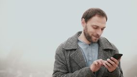 Foggy morning in Paris, France. Handsome man using the smartphone with touchscreen near the Eiffel tower. Portrait of beautiful male browsing the Internet stock video footage
