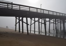 Foggy Morning with Pier and Family in the background. Newport Beach Balboa Pier with locals enjoying the ocean on a misty morning stock photography