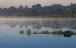 Foggy morning on the river. Foggy morning at the bank of the river, the island in the middle of the river with flowers and boat royalty free stock photo