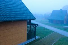 Foggy morning. Scenic landscape. Wooden houses royalty free stock photos