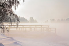 Foggy morning sunlight in winter landscape. Foggy morning sunlight in winter snowy landscape, pier at seashore Stock Images