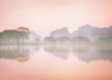 Foggy morning with trees reflection in lake. Hpa An, Myanmar. Amazing watercolor view of foggy morning landscape with trees reflection in lake water. Hpa An stock photo