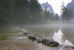 Foggy lake flowing over rocks stock photography
