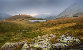 Foggy Mountain Landscape with a Tarn at Sunset Stock Photo