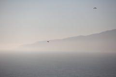 Foggy mountain and ocean Royalty Free Stock Photos