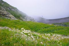 Foggy mountain road. View of mountain road with rocks and green grass with a lot of mist stock images