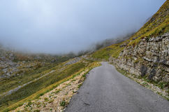 Foggy mountain road. Narrow mountain asphalt road, winding and dangerous, leading to low clouds Royalty Free Stock Photos