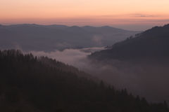 Foggy mountain valley at sunrise Stock Photo