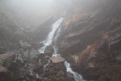 Foggy mystery waterfall. With rocks in Ukraine Stock Images