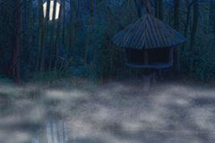Foggy night in the jungle, mist above the water and a bright moon in the sky, wooden tree hut at the river side. A foggy night in the jungle, mist above the royalty free stock photo