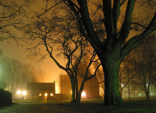 Foggy night in the park. Light streaming out of the church in the background stock image