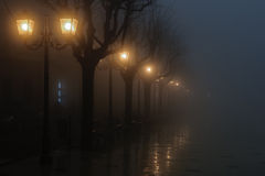 A foggy night. A square illuminated only by lamps in a foggy evening stock photos