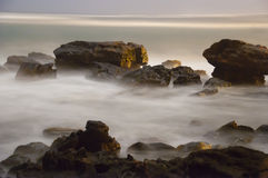 Foggy Ocean Sea Mist. Beautiful ocean sea foggy mist coming around rocks stock photography