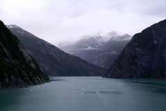 Foggy Peaks in Tracy Arm Fjords. Snow-capped mountains shrouded in fog as seen from inside Tracy Arm Fjords. Alaska's Inside Passage Royalty Free Stock Photo