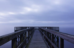 Foggy Pier Stretching into the Distance. A pier appears to float within a sea of fog stock photo