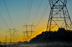Foggy power lines. A foggy sunrise over a field of power lines Royalty Free Stock Images
