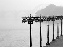 Foggy promenade on morning. Lanterns on foggy river promenade black and white Royalty Free Stock Images