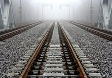 Foggy railroad track. Scenic view of straight railway or railroad track receding into distance on foggy day Stock Photo