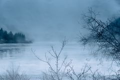 Rain and mist on ice covered northern lake in winter stock photos