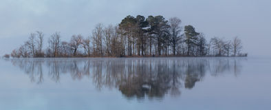 Foggy reflective island on calm glassy water Royalty Free Stock Photo
