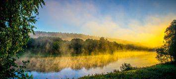 Foggy river at dawn. Scenic landscape near forest royalty free stock photos