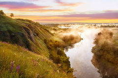 Foggy river and meadow at sunrise. Summer landscape. Misty morning. Colorful scenery. Beautiful dawn Royalty Free Stock Image