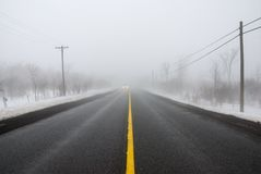 Foggy Road. Approaching headlights in heavy fog on road in winter; wide angle view Stock Photography