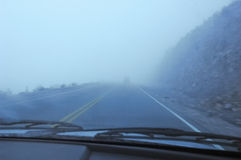 Foggy road from inside a car Stock Images