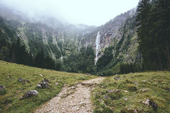 Foggy road leads to the waterfall. Royalty Free Stock Images