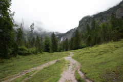 Foggy road leads to the waterfall. Royalty Free Stock Photo