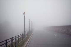 Foggy road with old lamps Royalty Free Stock Photos