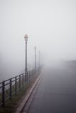 Foggy road with old lamps Stock Photography