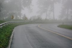 Foggy rural asphalt highway perspective with white line, misty road, Road with traffic and heavy fog. Bad weather driving royalty free stock images